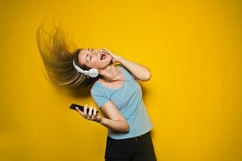 mulher com fones de ouvido a dançar ao escutar música